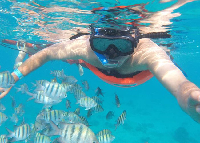 Kahleb feeding fish while snorkeling a shallow reef in Cozumel.